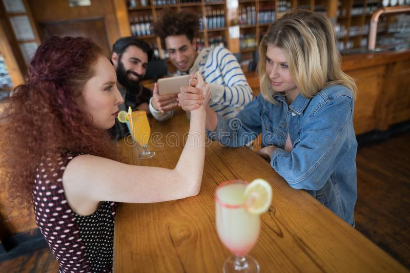 Women arm wrestling and men capturing a shoot. In bar stock image