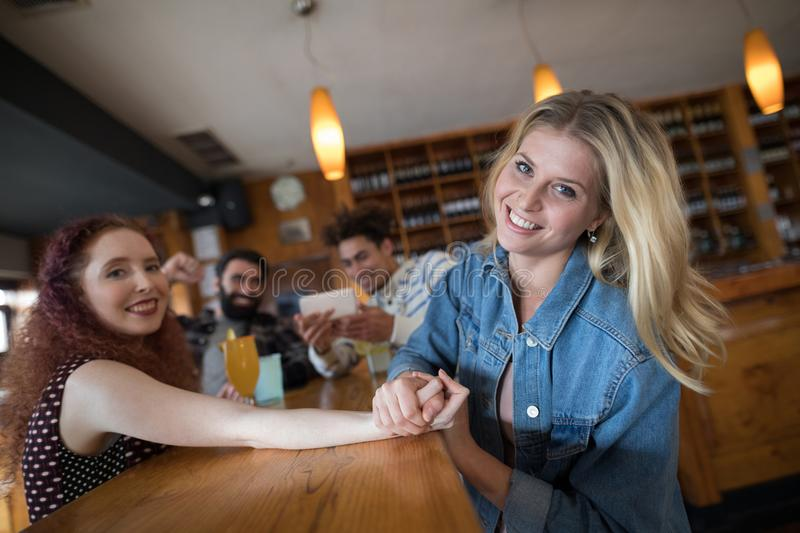 Women arm wrestling and men capturing a shoot. In bar royalty free stock images