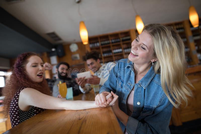 Women arm wrestling and men capturing a shoot. In bar royalty free stock photo