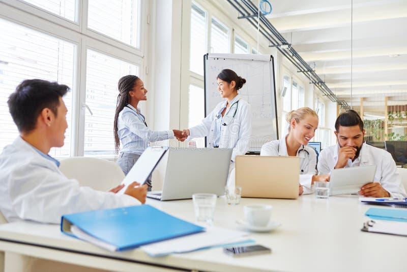 Women as doctors shaking hands stock photo