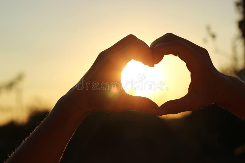 Women& x27; as mãos de s são cruzadas sob a forma do coração através de que o sun& x27; os raios fazem a maneira no por do sol fotografia de stock