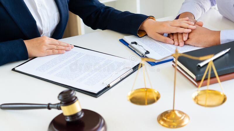 Women attorney or lawyer provide holding hands to Consoling with client trust commitment  in office, legal advice law concept stock photo