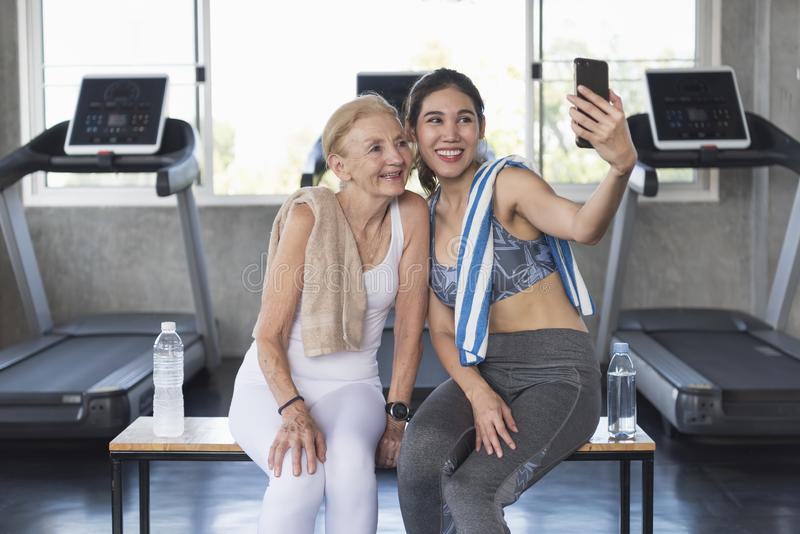 Women attractive smiling active fitness couple sitting in gym and taking a selfie stock photos