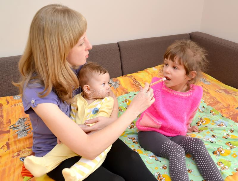 The woman with the baby on hands gives to the sick girl medicine by means of the batcher. Treatment stock photos