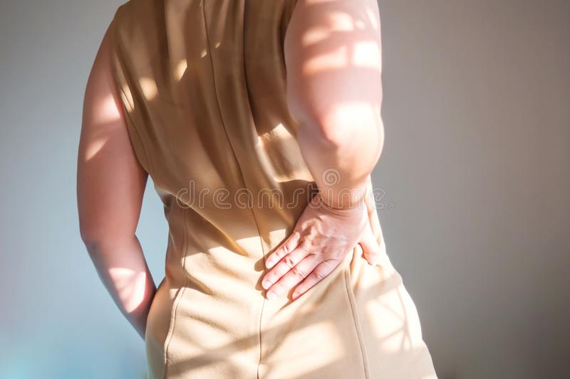 Women are back pain. Used hand support at waist. stock photos