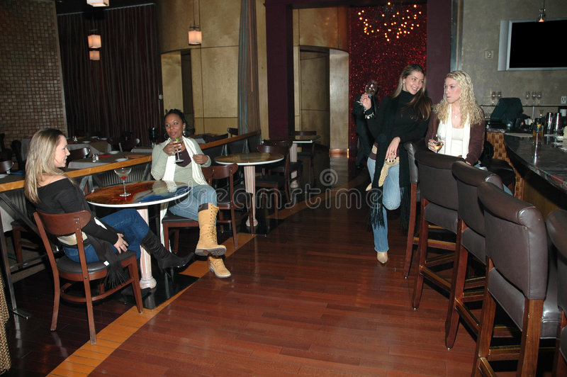 Women at the Bar. Women having a drink at the bar and meeting friends. Women talking to each other in a restaurant or bar royalty free stock images