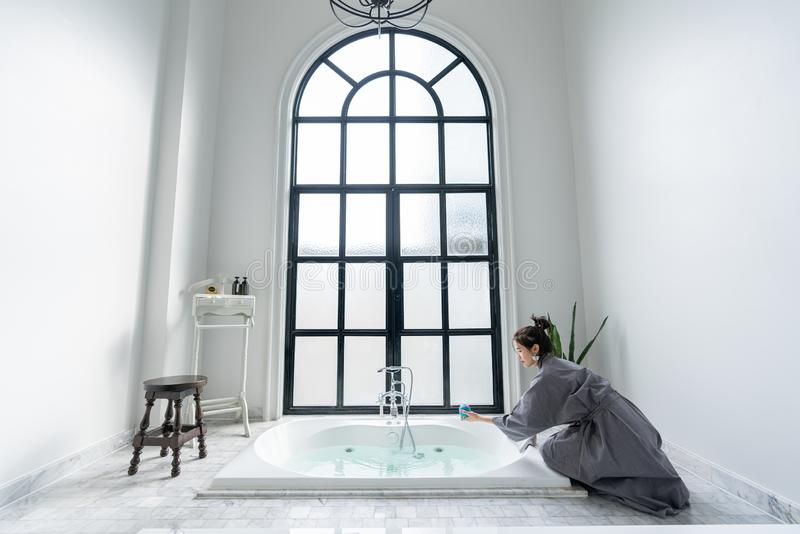 Women in bathrobe while carryin bathbomb in nice design jacuzzi bathtub with high transparant window in natural light setting. Scene / cozy interior concept / royalty free stock photography