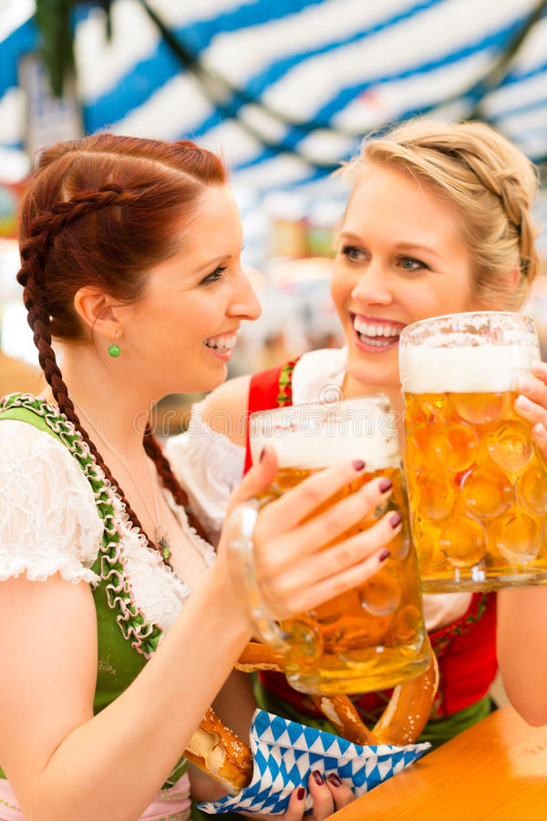 Women with Bavarian dirndl in beer tent. Young women in traditional Bavarian clothes - dirndl or tracht - on a festival or Oktoberfest in a beer tent stock photography
