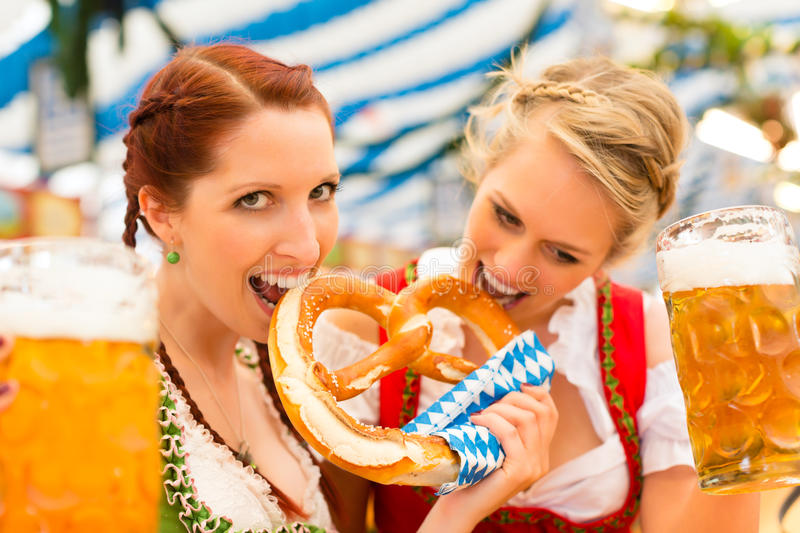 Women with Bavarian dirndl in beer tent. Young women in traditional Bavarian clothes - dirndl or tracht - on a festival or Oktoberfest in a beer tent royalty free stock photo