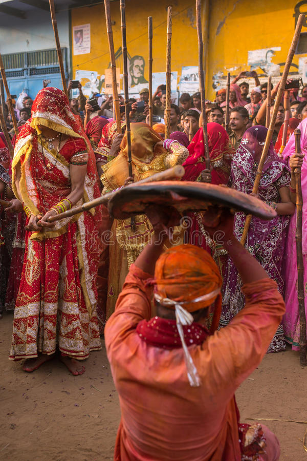 Women beat up men with long sticks as a ritual in the Lathmar Holi celebration in Nandgaon, India. Nandgaon, India - March 18, 2016: Women beat up men with long royalty free stock images