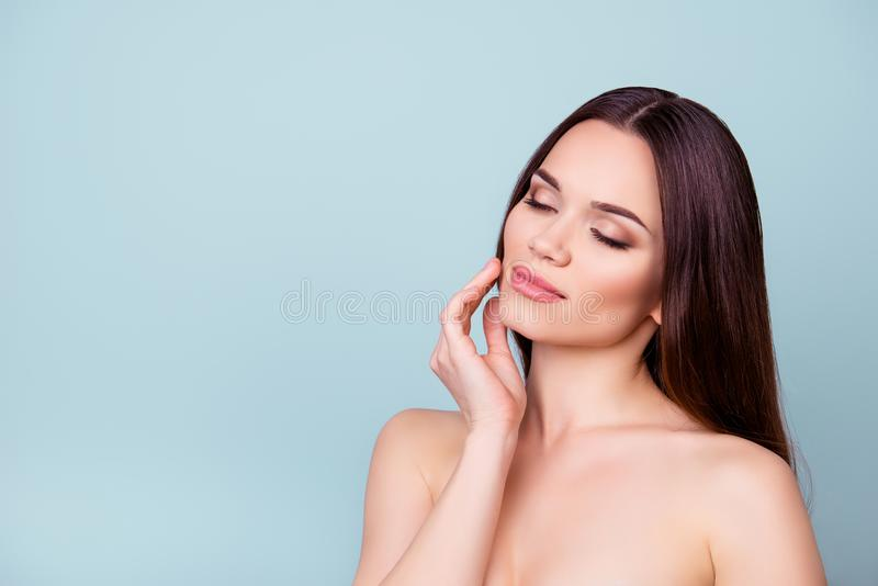 Women beauty and health, wellbeing concept. Young pretty brunette lady is touching gently her attractive healthy smooth skin royalty free stock photo