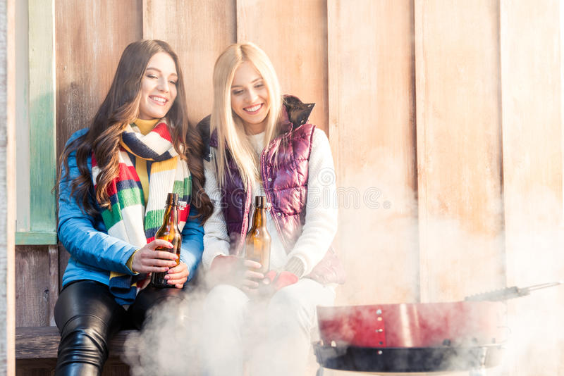 Women with beer in hands looking at barbecue. Smiling women with beer in hands looking at barbecue royalty free stock images