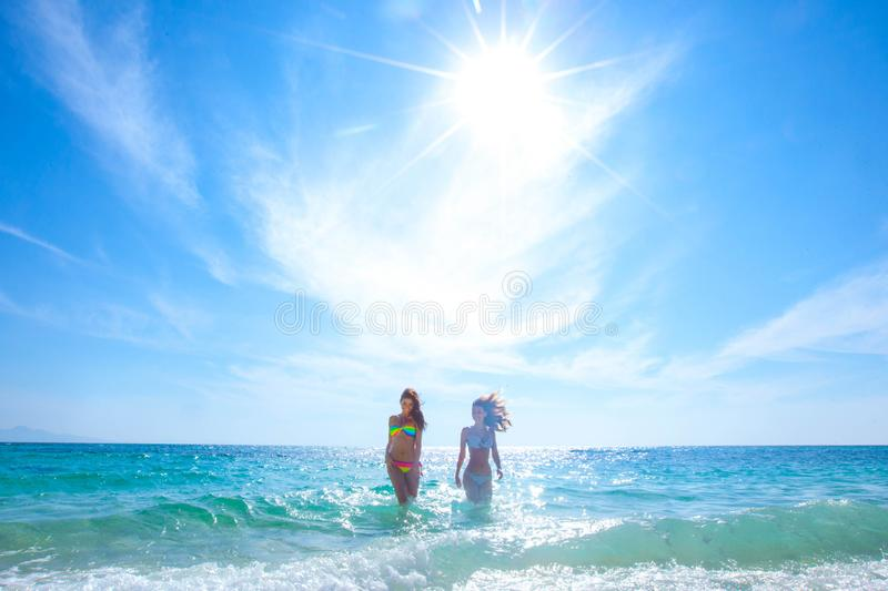Women in bikni run to beach stock images
