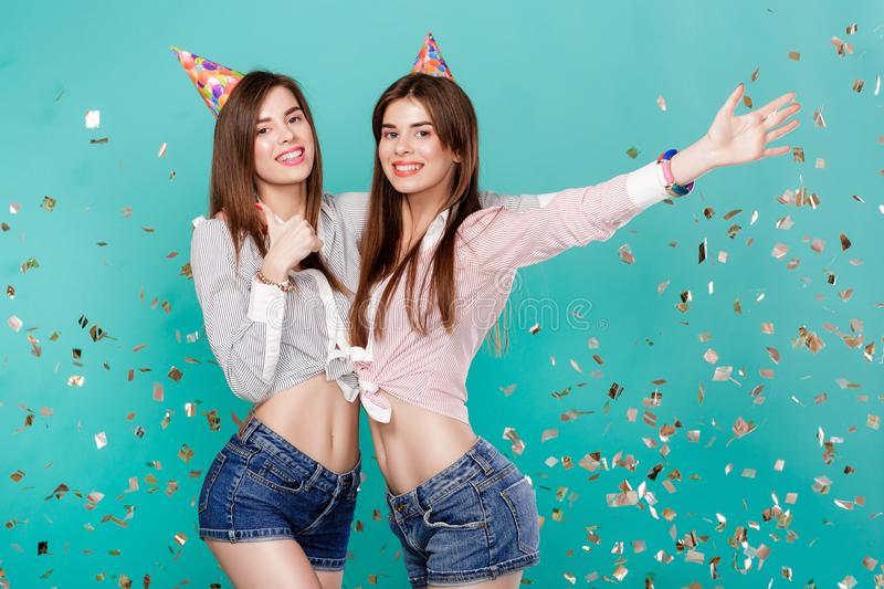 Women in birthday hat and confetti on blue background. Funny female twins in birthday hat and gold confetti on blue background. Celebration and party. Having stock photography