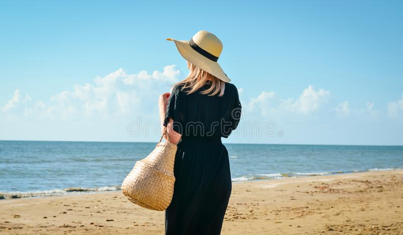 Women   with  black dress and   straw hat relaxing on  beach at sunset. Caucasian girl  with  black dress and   straw hat relaxing on  beach at sunset stock photography