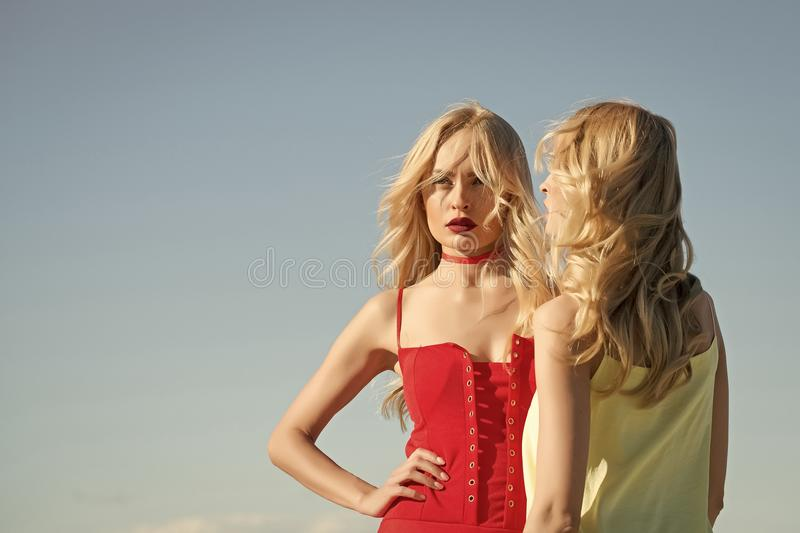 Women with blonde hair outdoor. Twins in summer on blue sky background. Beauty and fashion, look. Girls with legs, family and sisters. Freedom and family royalty free stock images