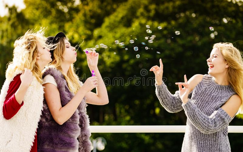 Women blowing soap bubbles, having fun stock photo