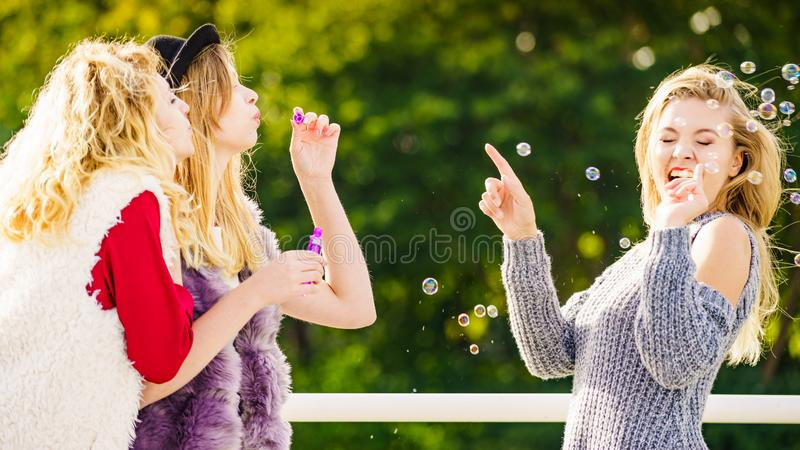 Women blowing soap bubbles, having fun royalty free stock photos