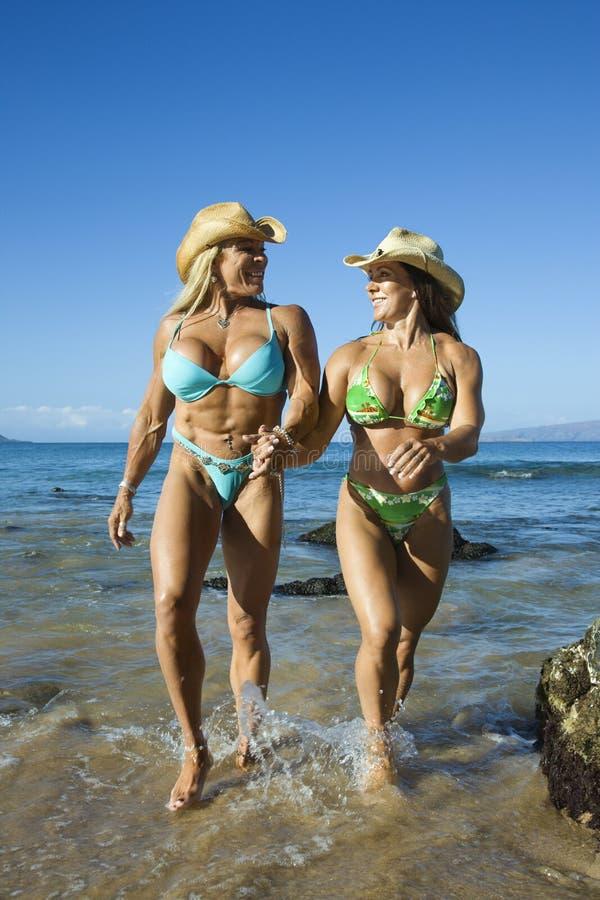 Women bodybuilders at beach. stock image