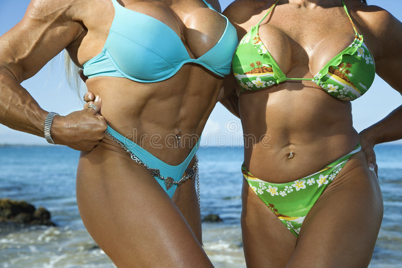 Women bodybuilders at beach. royalty free stock photo