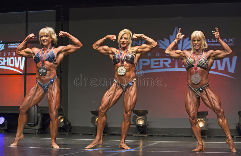 Women Bodybuilding Winners Display Medals and Biceps. The top three finishers of the Women's Bodybuilding competition display their medals and flex their biceps royalty free stock photos