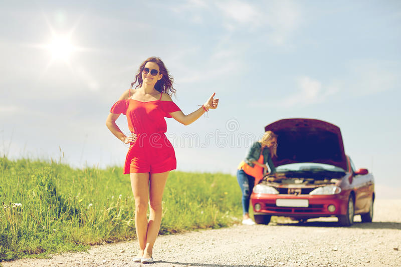 Women with broken car hitchhiking at countryside royalty free stock photo