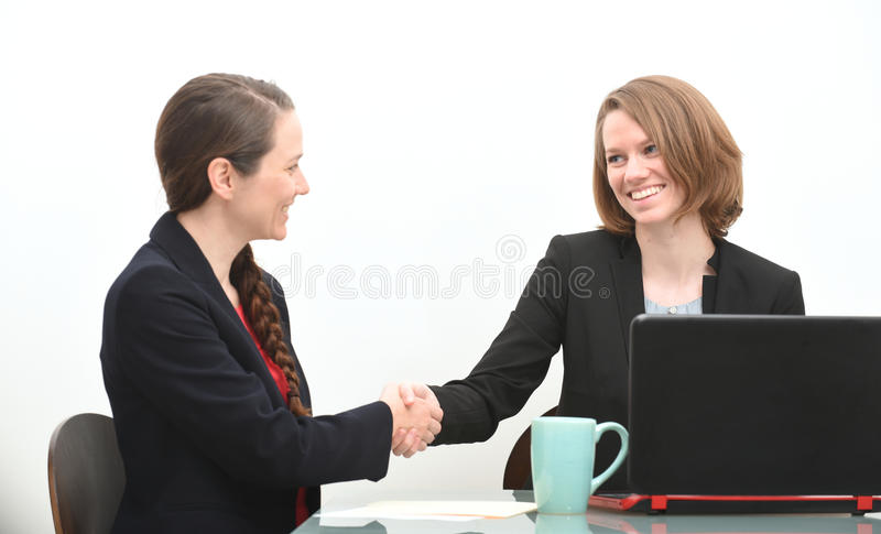 Women in business meeting or job interview. Business women in a job interview or business meeting shaking hands stock image