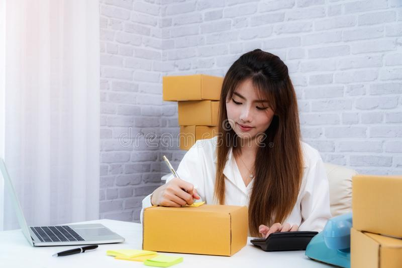 Women business owner writing address on packing box at workplace in home offce. online shopping SME entrepreneur or freelance stock photo