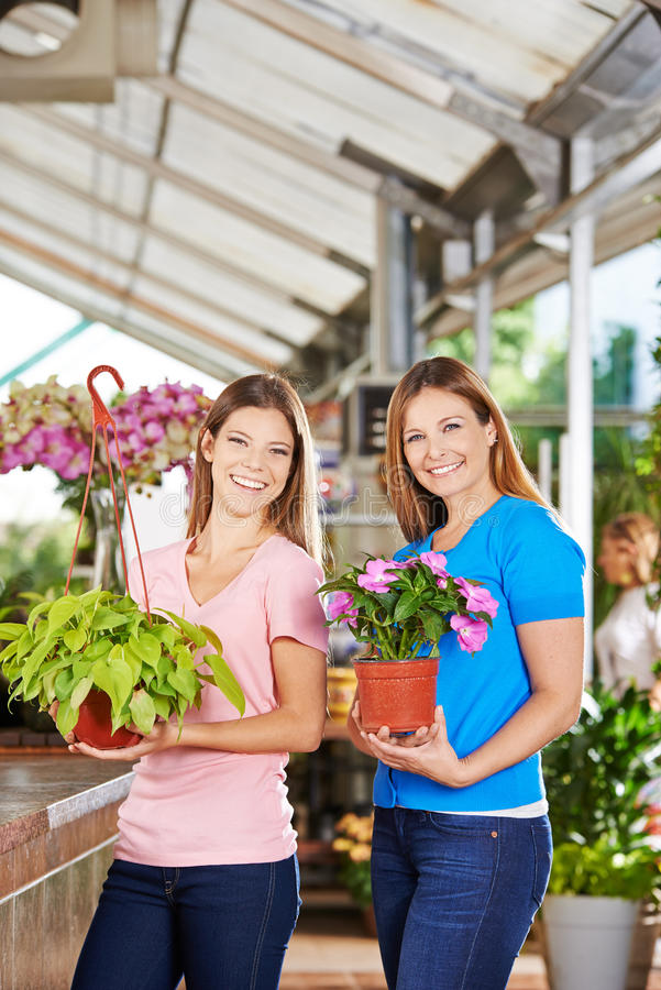 Women buying plants in nursery shop. Two happy women buying green plants in a nursery shop royalty free stock photography