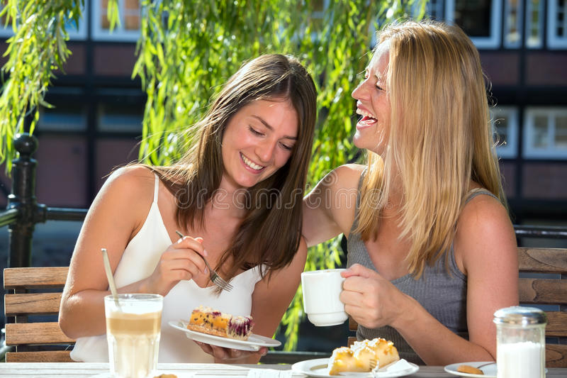 Women in cafe eating desert and laughing royalty free stock photos