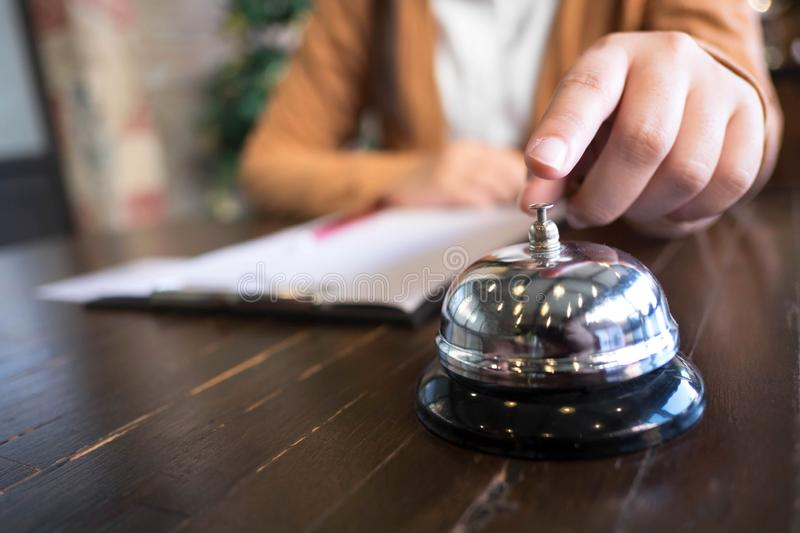 Women call hotel reception with finger push a bell in lobby hotel. hotel concept royalty free stock photography