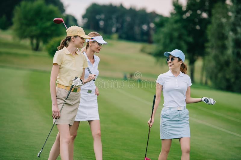 Women in caps with golf equipment having conversation. At golf course royalty free stock photography