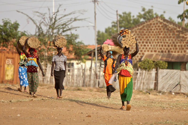 Women carrying loads in South Sudan. TORIT, SOUTH SUDAN-FEBRUARY 20, 2013: Unidentified women carry heavy loads on their heads in the village of Torit, South royalty free stock photo