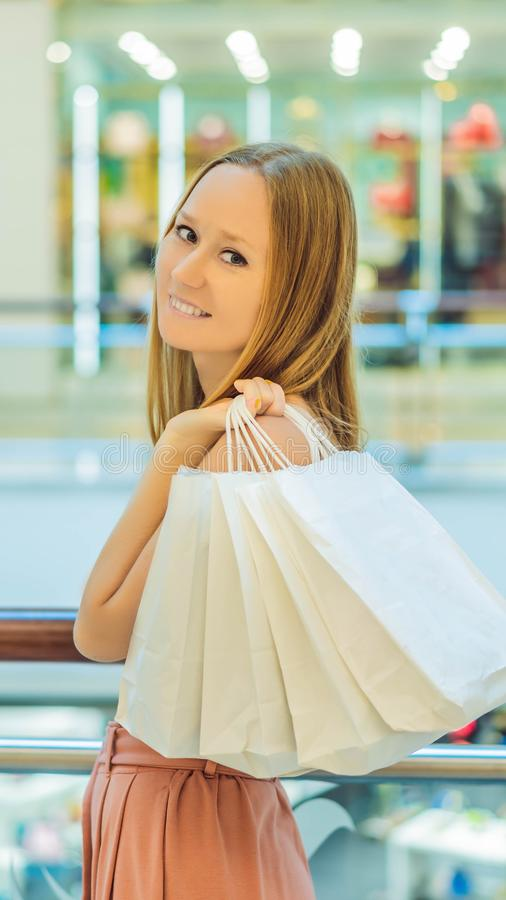 Women carrying a lot of shopping bags in blurred shopping mall VERTICAL FORMAT for Instagram mobile story or stories stock images