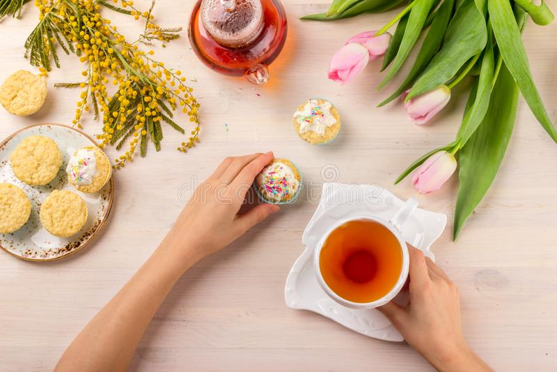 Women& x27 ; carte de voeux de jour de s avec les tulipes, la mimosa, le thé et les petits gâteaux sur le fond en bois photo stock