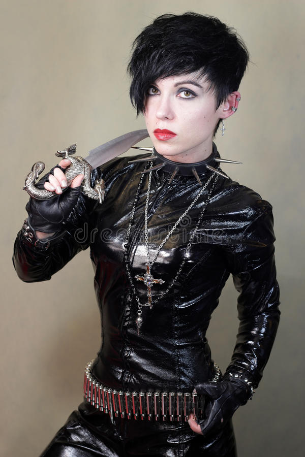 Women in cat suit. Young woman in black cat suit with knife stock image