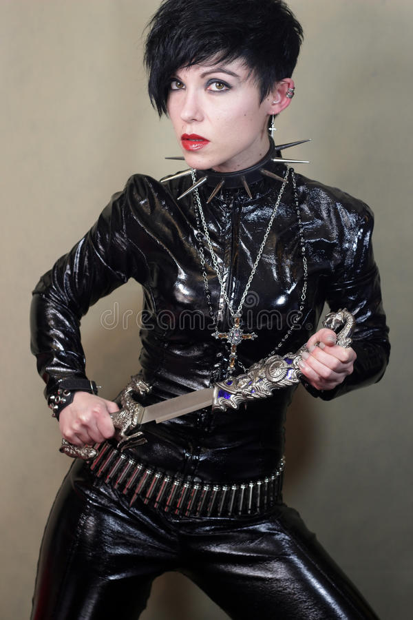 Women in cat suit. Young woman in black cat suit with knife stock images