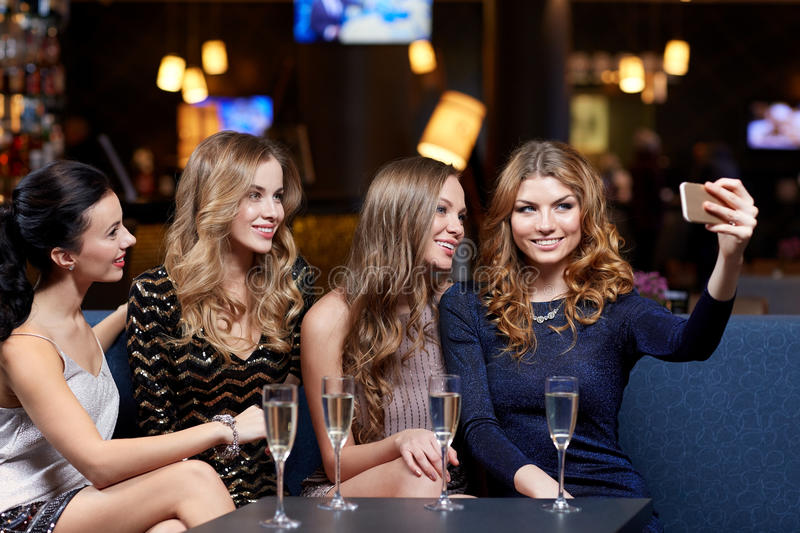Women with champagne taking selfie at night club royalty free stock photography