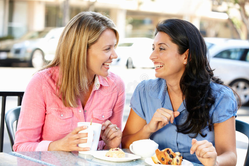 Women chatting over coffee and cakes. Having fun stock images