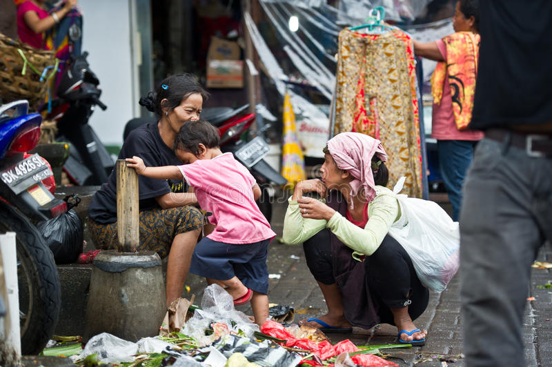Women and child in polluted market in Bali, Indonesia. Women talking while a child is climbing piles of junk and garbage in a market in Ubud, Indonesia. Bali is stock photo