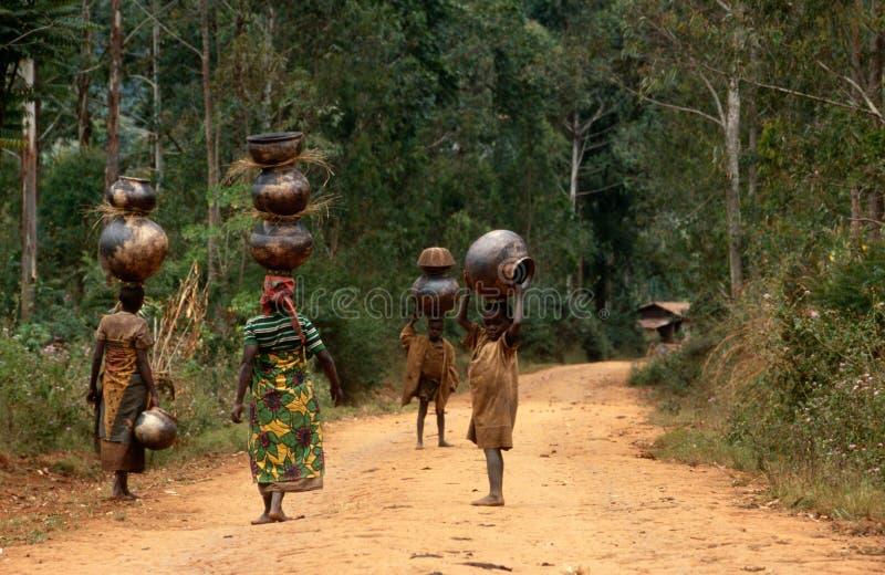 Women and children carrying pots in Burundi. stock photography