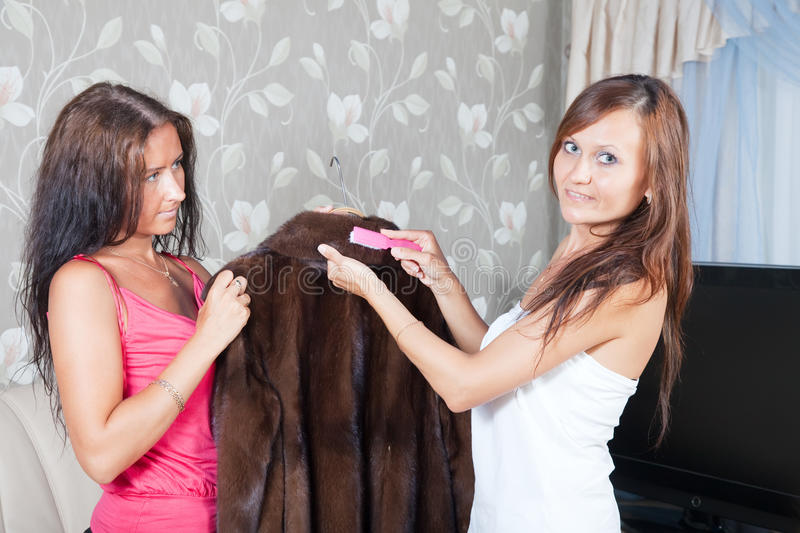 Women cleaning fur coat with whisk royalty free stock image