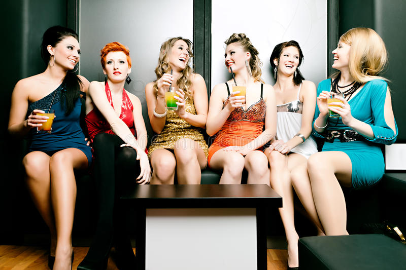 Women in club or disco drinking cocktails