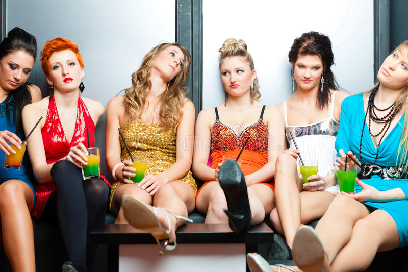 Women in club or disco drinking cocktails. Women or models in club or disco drinking cocktails having no fun as the party is boring royalty free stock image