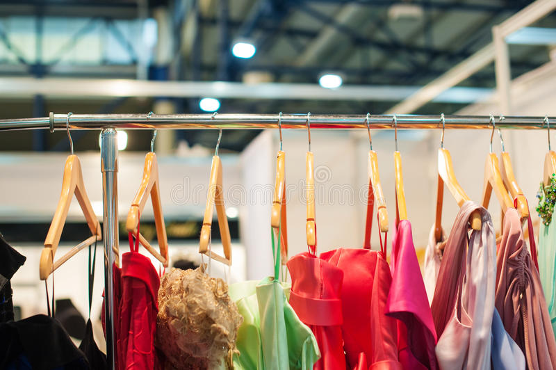Women colorful dresses hanging in the closet on trempel.  royalty free stock photo
