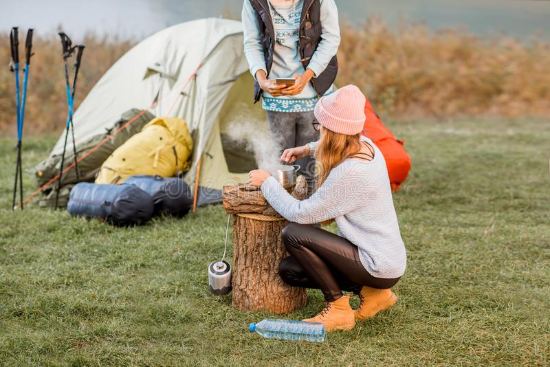 Women cooking food at the camping. Two women in sweaters cooking food for dinner during the outdoor recreation at the camping in the evening royalty free stock photos