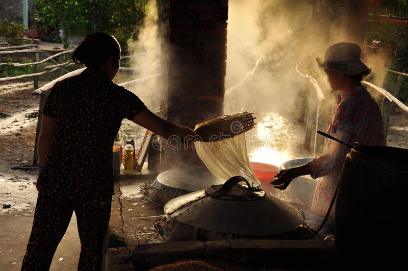Women cooking rice paste to make rice noodles, vietnam. Vietnamese cuisine. Women cooking rice paste dough to make rice noodle, Vietnam royalty free stock image