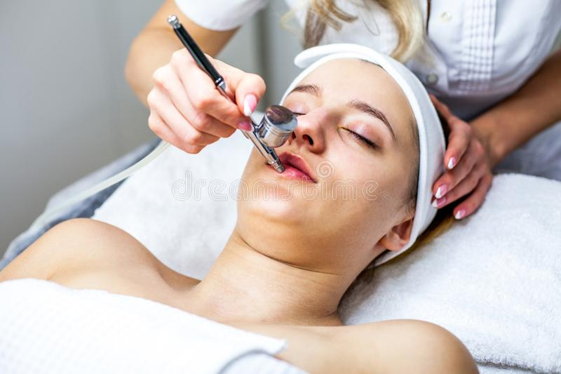 Women in cosmetology cabinet. Cosmetologist is doing procedure for young girl. stock photography