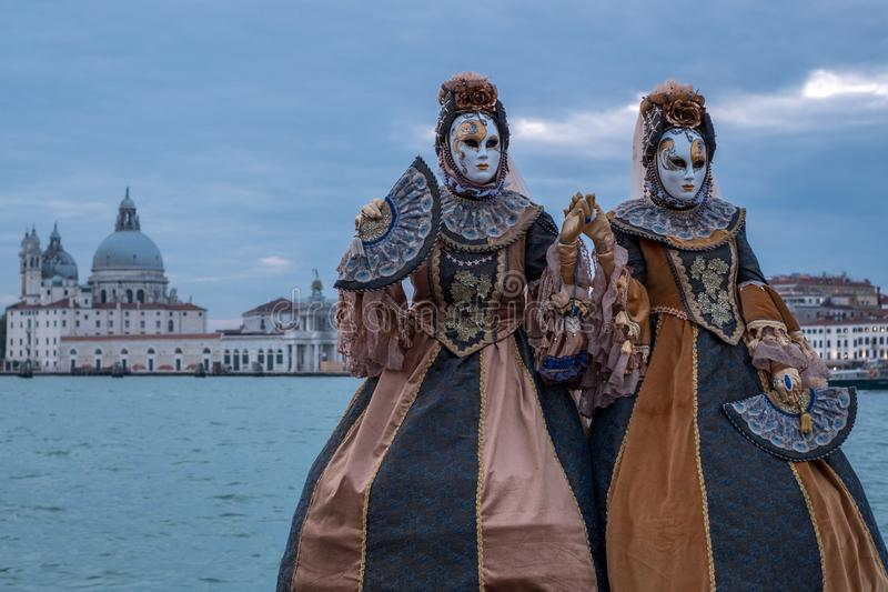 Women in costume standing in front of the the Grand Canal with the Salute Church in the background, during the Venice Carnival. Two women in traditional stock images