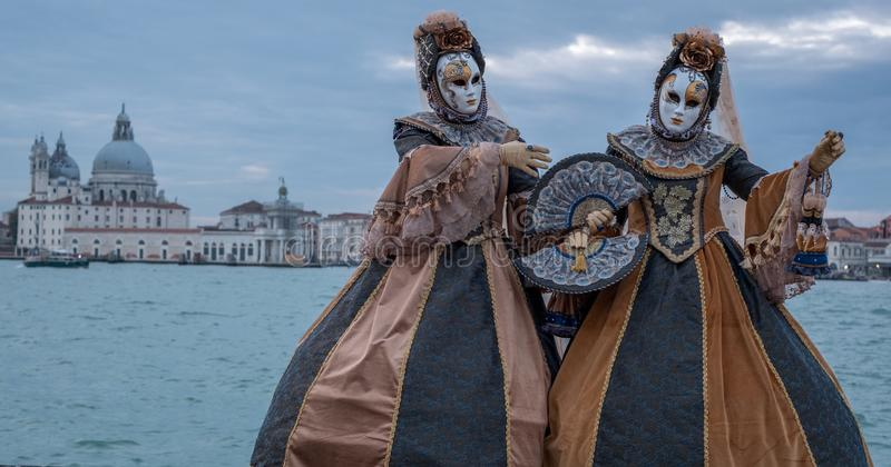 Women in costume standing in front of the the Grand Canal with the Salute Church behind, during the Venice Carnival. Two women in traditional costumes standing stock photography